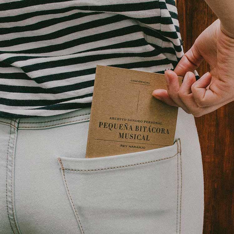 Persona guardando Pequeña bitácora musical en bolsillo trasero de pantalón